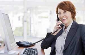 Happy young businesswoman talking on phone